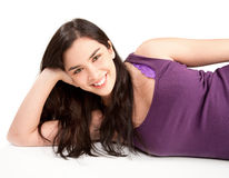 Smiling Young Woman Lying Down. A beautiful smiling young woman is lying down and relaxing while looking at the camera Royalty Free Stock Photography