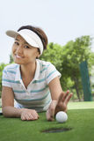 Smiling young woman lying down in a golf course getting ready to flick the ball into the hole Stock Image