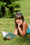 Smiling young woman lying down on grass with book Royalty Free Stock Images