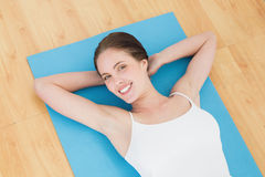 Smiling young woman lying on exercise mat Stock Photos