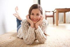 Smiling young woman lying on floor at home. Portrait of smiling young woman lying on floor at home Stock Images