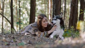 Smiling young woman lying in the forest and having a moment of tenderness with her darling pet stock video