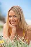 Smiling Young Woman Lying in Grass Royalty Free Stock Photography