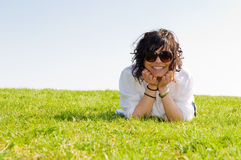 Smiling young woman lying on the grass Stock Photo