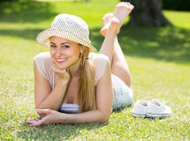 Smiling young woman lying on grass Royalty Free Stock Image