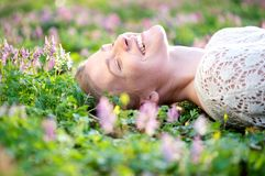 Smiling young woman lying in grass and flowers. Happy young female lying on a flower field Stock Image