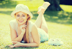 Smiling young woman lying on grass Stock Photo