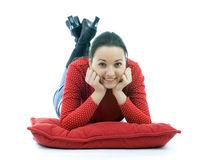 Smiling  young woman lying on the red pillow Stock Photos