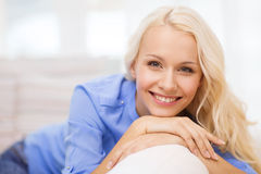 Smiling young woman lying on sofa at home. Home and happiness concept - smiling young woman lying on sofa at home royalty free stock photography