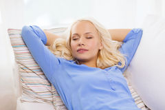 Smiling young woman lying on sofa at home Royalty Free Stock Image