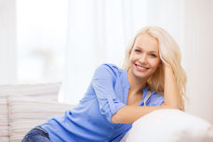Smiling young woman lying on sofa at home Stock Images