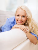 Smiling young woman lying on sofa at home Royalty Free Stock Photos