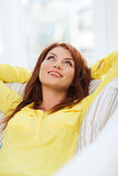Smiling young woman lying on sofa at home Stock Photography