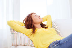 Smiling young woman lying on sofa at home Royalty Free Stock Images