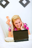 Smiling young woman lying on sofa and using laptop Stock Photos