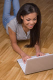 Smiling young woman lying on wood flooring. Stock Image