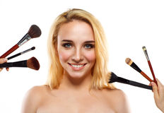 Smiling young woman with makeup brushes near her face Royalty Free Stock Image