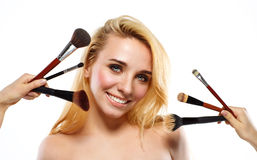 Smiling young woman with makeup brushes near her face Stock Photos