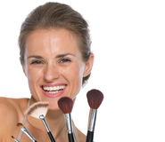 Smiling young woman with makeup brushes Royalty Free Stock Image