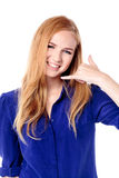 Smiling young woman making a call me gesture Stock Photo