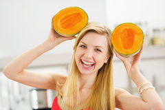 Smiling young woman making ears with two slices of melon Stock Photo