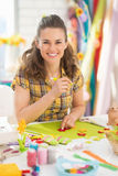 Smiling young woman making easter decoration Stock Images