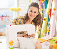 Smiling young woman making easter pot holder mitts Stock Photo