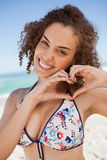 Smiling young woman making a heart with her hands Royalty Free Stock Photo