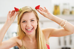 Smiling young woman making horns with strawberries Royalty Free Stock Image