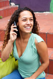 Smiling young woman making a phone call. Portrait of a smiling young woman talking on mobile phone while sitting on steps outdoors Stock Images