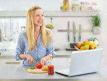 Smiling young woman making snacks in kitchen Royalty Free Stock Photography