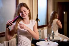 Woman making a hairstyle at home. Smiling young woman making a styling using hair straightener in front of the mirror in bathroom stock photography