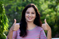 Smiling young woman making thumbs up gesture Royalty Free Stock Photos