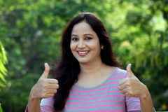 Smiling young woman making thumbs up gesture Royalty Free Stock Image