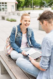 Smiling young woman with male friend studying on bench at college campus Royalty Free Stock Photo