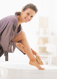 Smiling young woman massaging leg in bathroom Stock Images