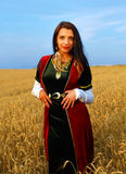 Smiling Young woman with medieval dress standing on a wheat field with sunset. Natural background. Stock Image