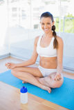 Smiling young woman meditating in lotus position Royalty Free Stock Photos