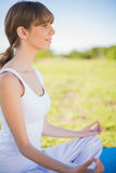 Smiling young woman meditating in lotus position Royalty Free Stock Images
