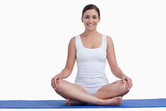 Smiling young woman meditating on a yoga mat Stock Photography