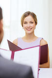 Smiling young woman with menu at restaurant Stock Photos
