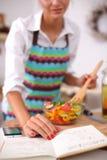 Smiling young woman  mixing fresh salad Stock Photos