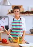 Smiling young woman mixing fresh salad Royalty Free Stock Photos
