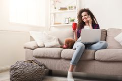 Smiling young woman with mobile, laptop and little dog at home. Happy girl with smartphone, laptop and dog at home. Curly woman talking on mobile, surfing the royalty free stock images