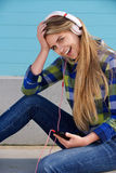 Smiling young woman with mobile phone and headphones Royalty Free Stock Photos