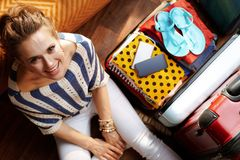 Smiling young woman in modern living room in sunny summer day. Upper view of smiling young woman in white pants and striped blouse in the modern living room in stock photography
