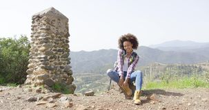 Smiling young woman on mountain. Young beautiful female sitting on rock near stone small tower on top of mountains and smiling stock footage