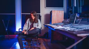 Smiling young woman music composer in recording studio. Smiling young woman sitting at music mixing desk. happy female sound engineer at sound recording studio stock image