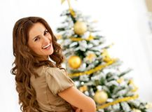 Young woman near christmas tree. Smiling young woman near christmas tree Royalty Free Stock Photos