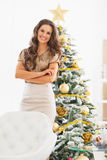 Smiling young woman near christmas tree. In living room Royalty Free Stock Photo